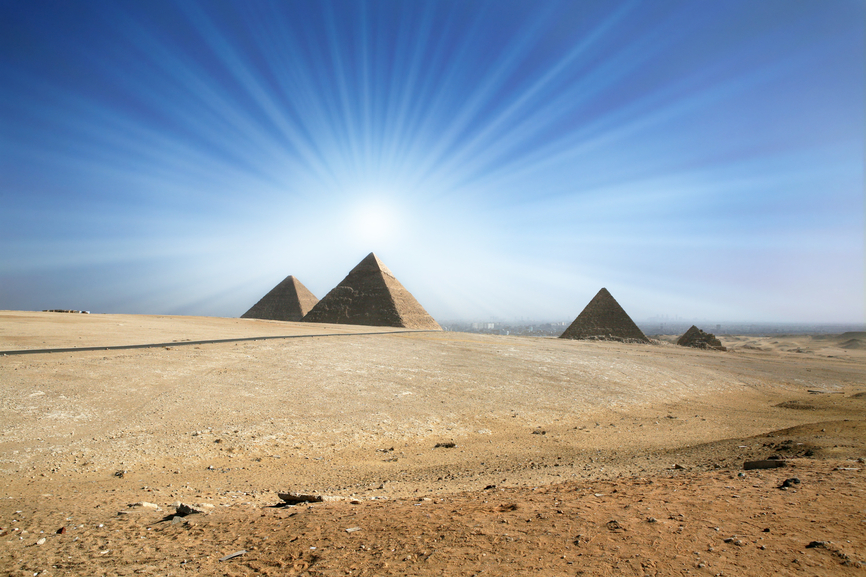 Light of the sun in the sky over an ancient pyramid.