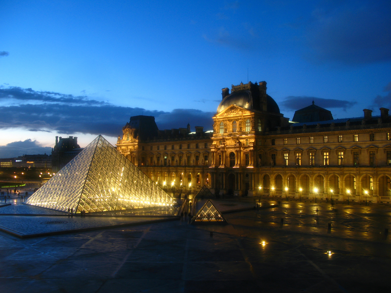 The most visited museum in the world, Louvre in Paris, France magnificent illuminated at twilight, as seen from the Denon Wing. Its history goes back 800 years of continuous transformations from fortress to palace and today museum.  Mona Lisa by Leonardo Da Vinci is only one of the works of art exhibited today inside. Image taken through an old thick and irregular glass, and lights have a special glow due to this fact.