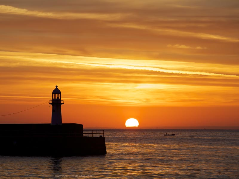 silloutte of the harbour lighthouse in St Ives, Cornwall with the golden sun rising over the Atlantic ocean