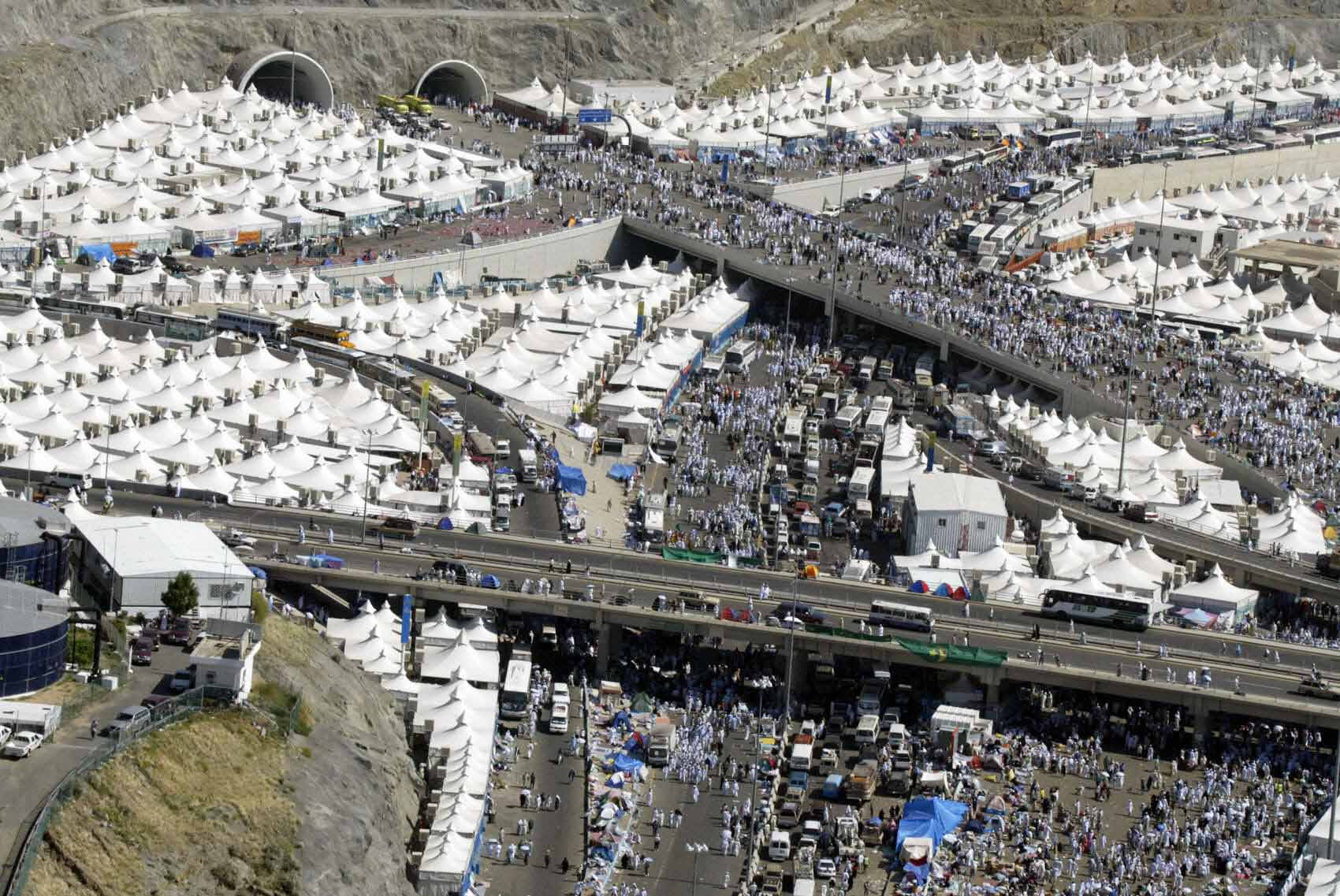 """An aerial view of Mina, near Mecca, shows scores of Muslim pilgrmis walking towards the spot where they stone the devil, one of the rituals of the last stage of the annual hajj pilgrimage, on second day of Eid Al-Adha, 02 February 2004. Saudi Arabia's King Fahd has ordered """"overall plans"""" to be drawn up to modernise the holy cities of Mecca and Medina after 251 pilgrims died in a stampede, according to the official Saudi media. AFP PHOTO/Awad AWAD"""