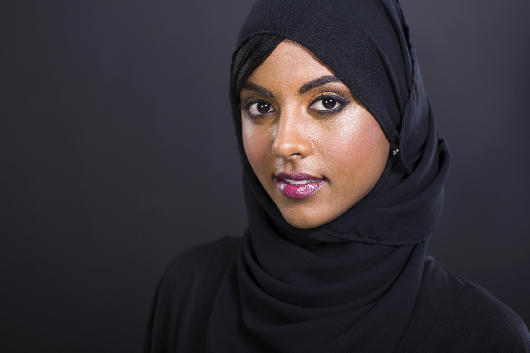 pretty young muslim woman head shot over black background